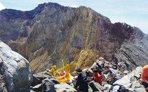 アグン山の頂稜で登山ガイドと安全登山を祈願