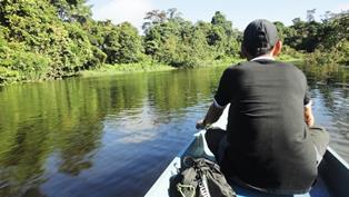 ロングボートで川をさかのぼり、洞窟へアプローチする