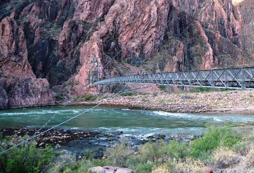 谷底のコロラド川に架かる橋を渡る