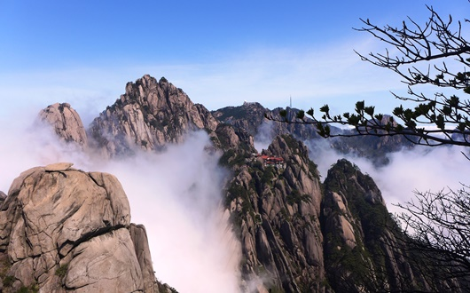 黄山の三大主峰の一つ天都峰から望む最高峰・蓮花峰(1,864m)と赤い屋根の玉塀楼