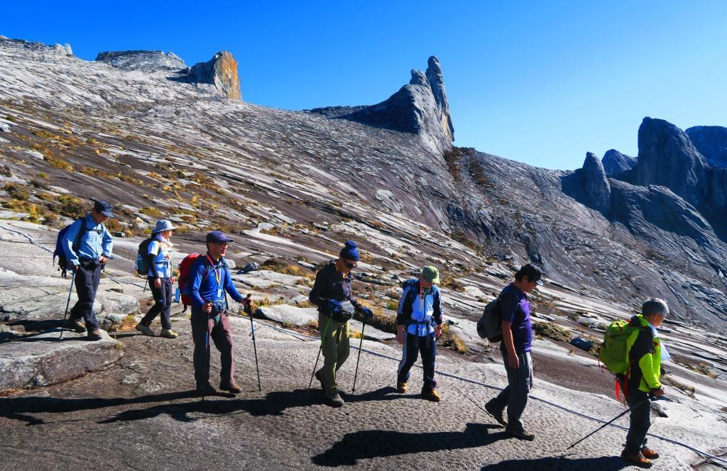 特異な岩峰ドンキーイヤーズをバックに頂上台地を下る