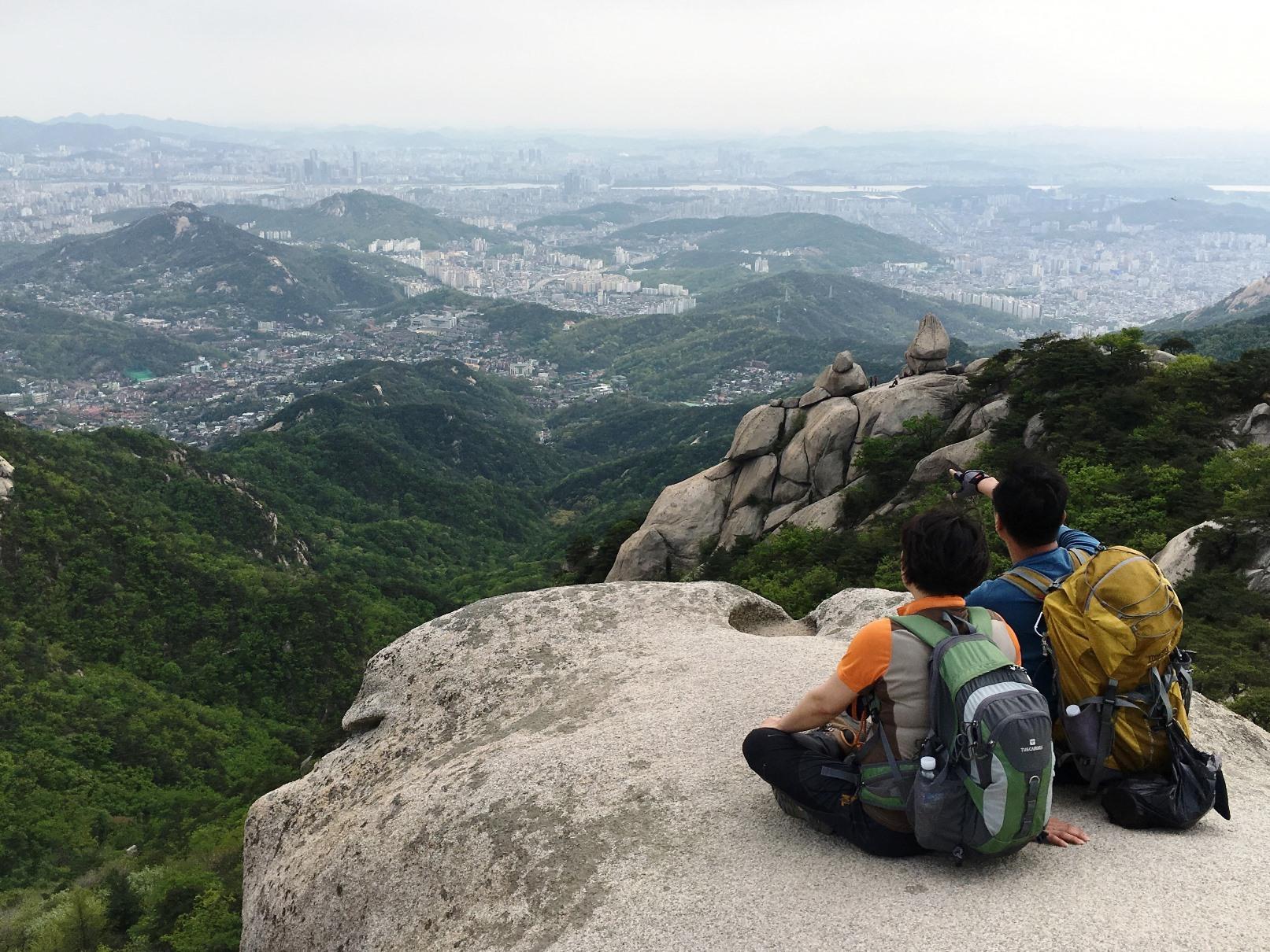 北漢山から高層ビル群が連なるソウルの街並みを一望
