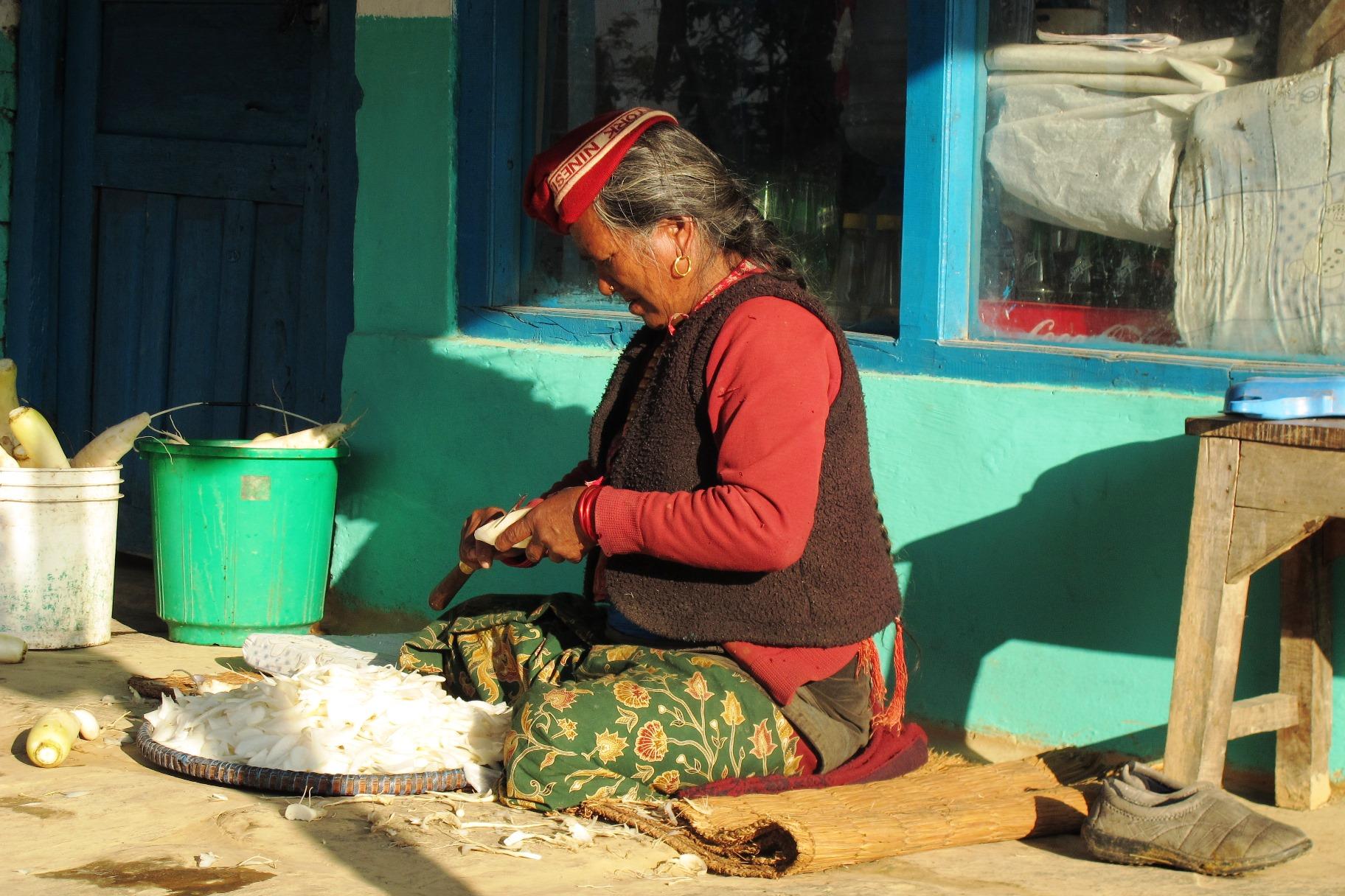軒先で農作業をする老人