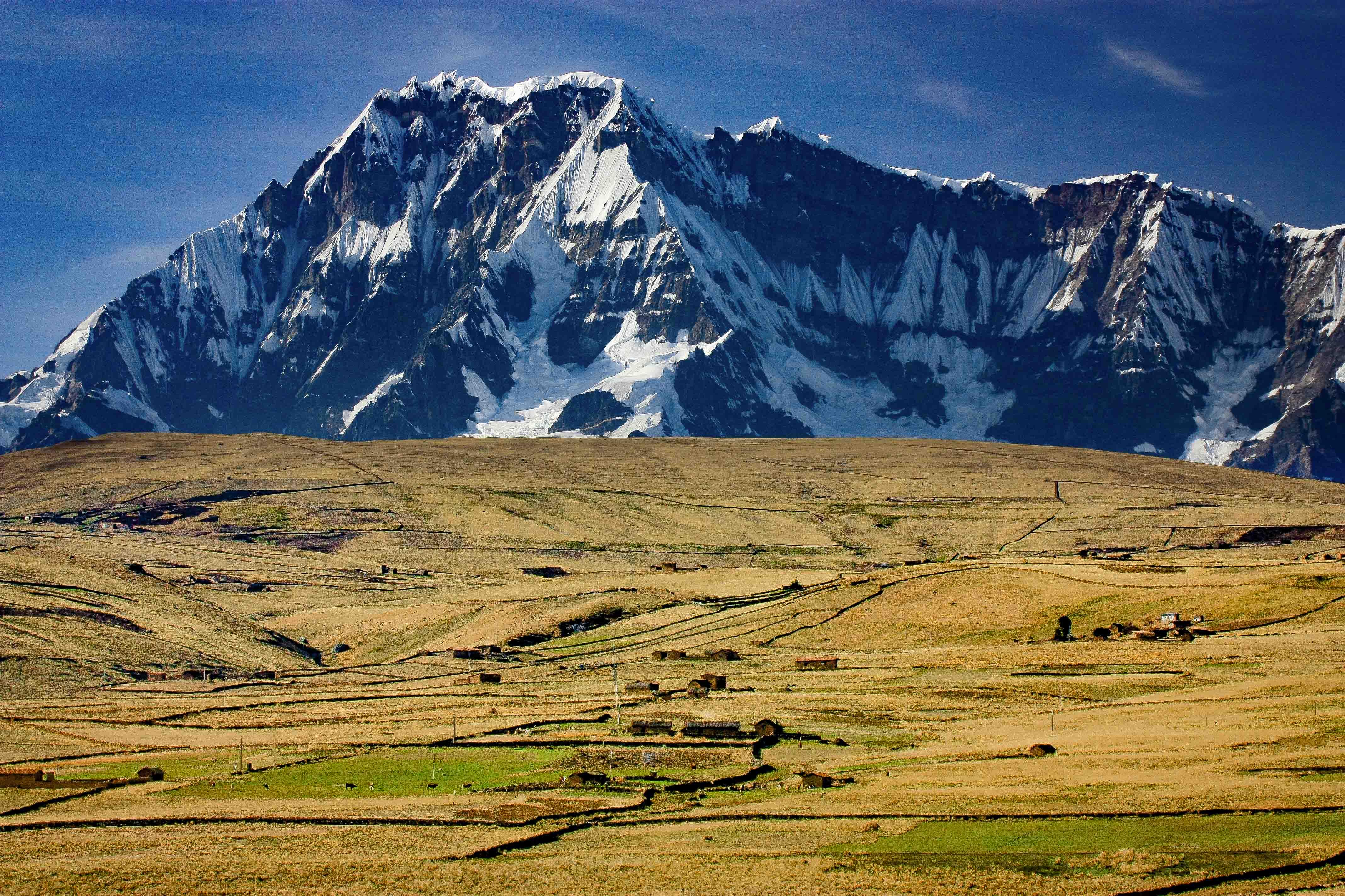 山麓に生きる集落と大草原の彼方に聳えるビルカノータ山群の主峰アウサンガテ(6,394m)