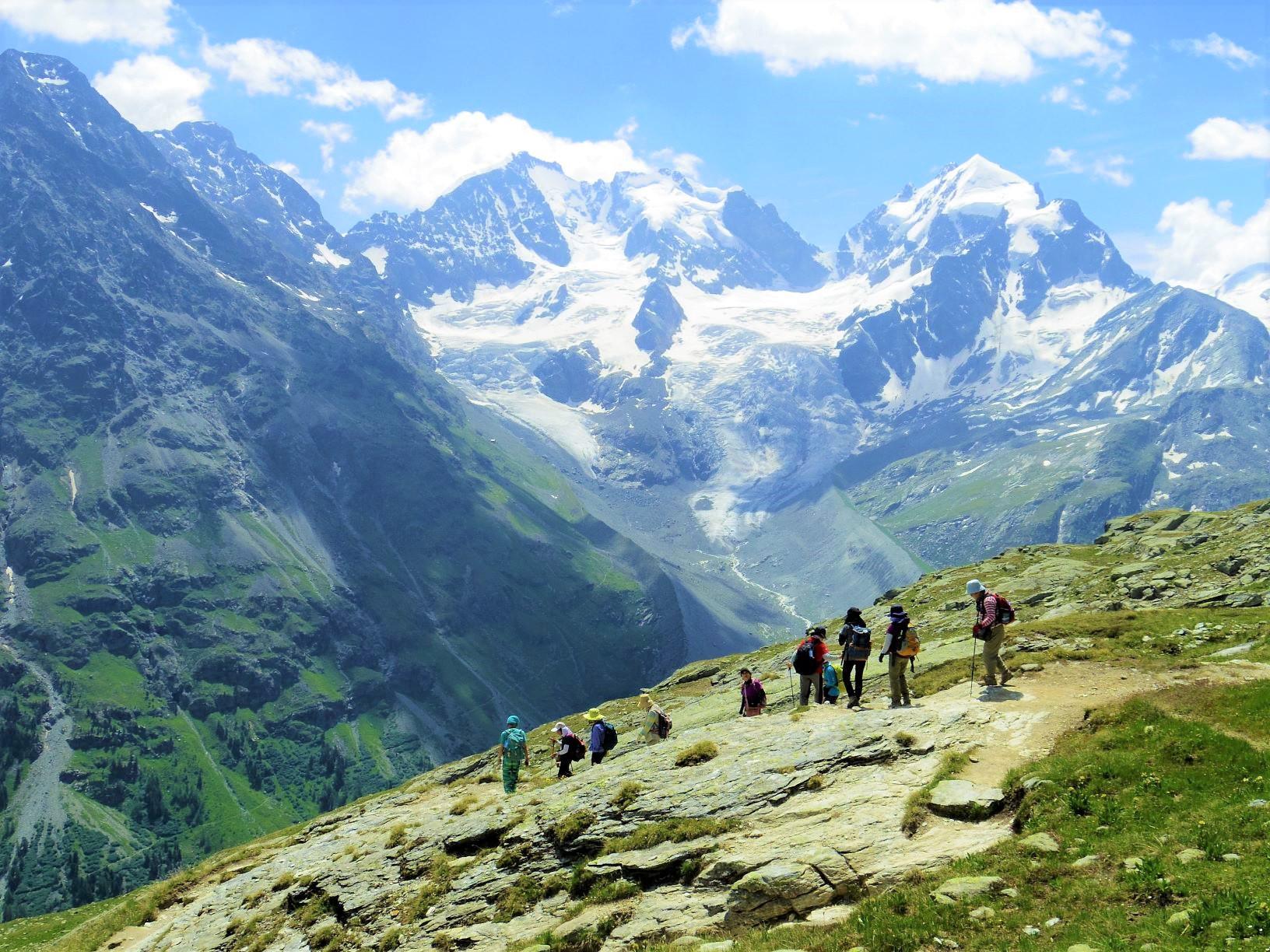 ベルニナ山群展望ハイキング(3日目)。背後に山群最高峰ピッツ・ベルニナ(4,049m、中央)がそびえる(3日目)