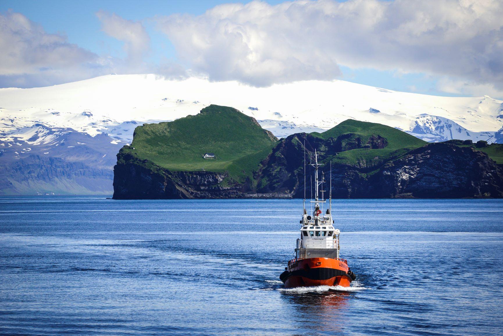 氷雪抱く雄大な山と緑美しい海岸線をバックに漁船がいく、探検船だからこそ見られるアイスランドの魅力に迫る旅