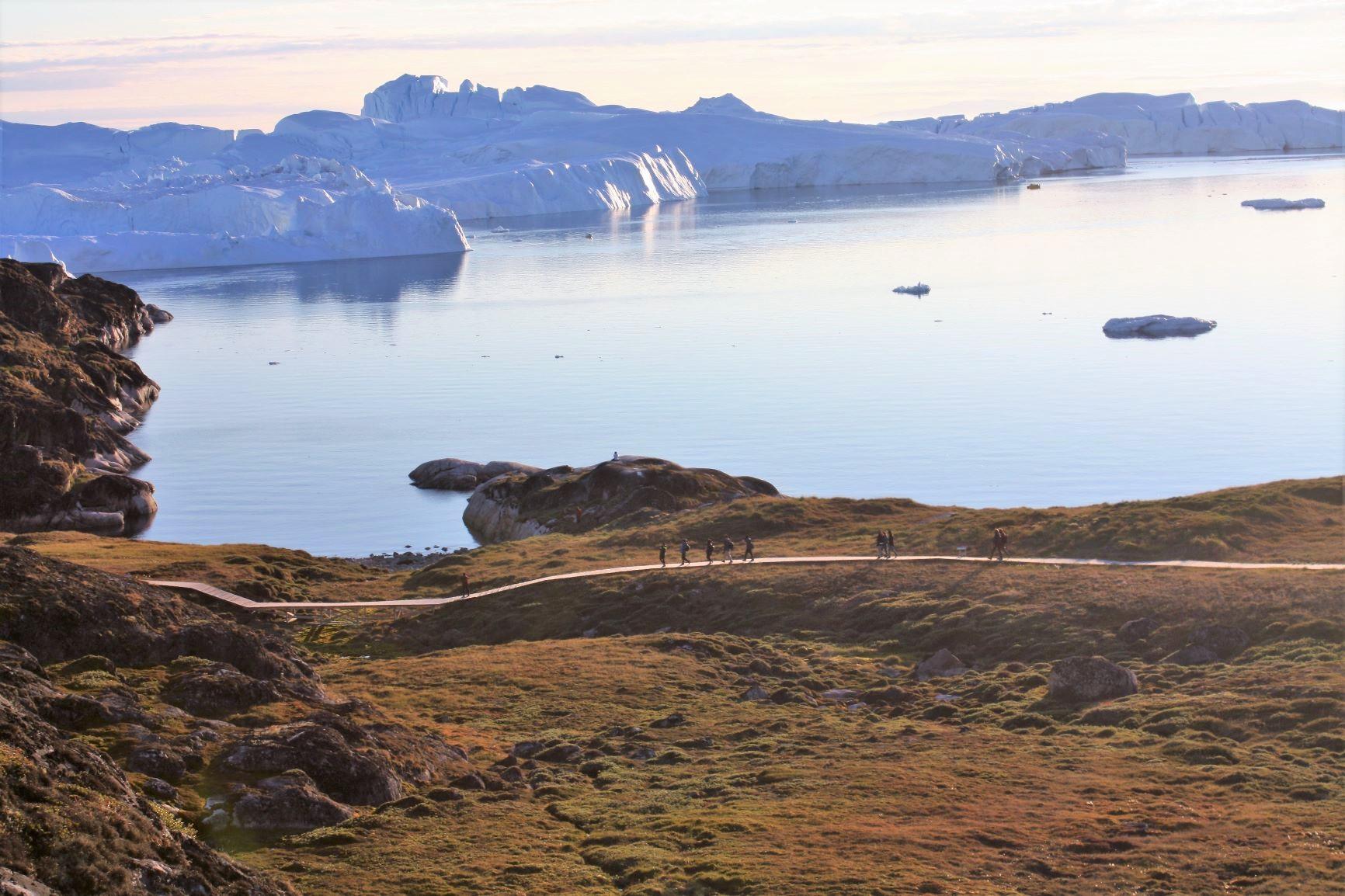 極地ならではのやわらかい斜光の中、氷山が浮かぶ海を眺めながら歩く